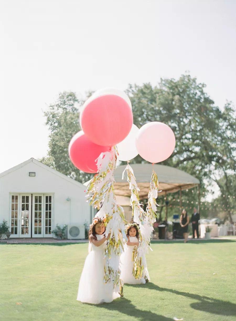 Flower girls carrying big pink tasseled balloons