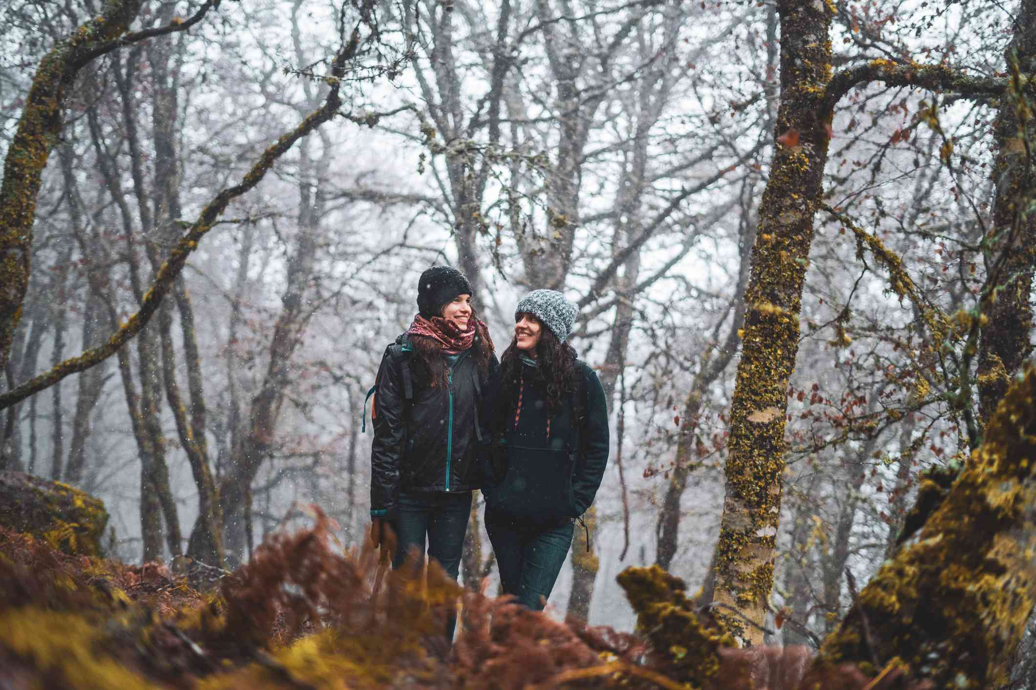 Female couple walking in the woods during winter