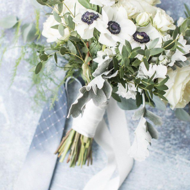 a white bouquet with blue tie