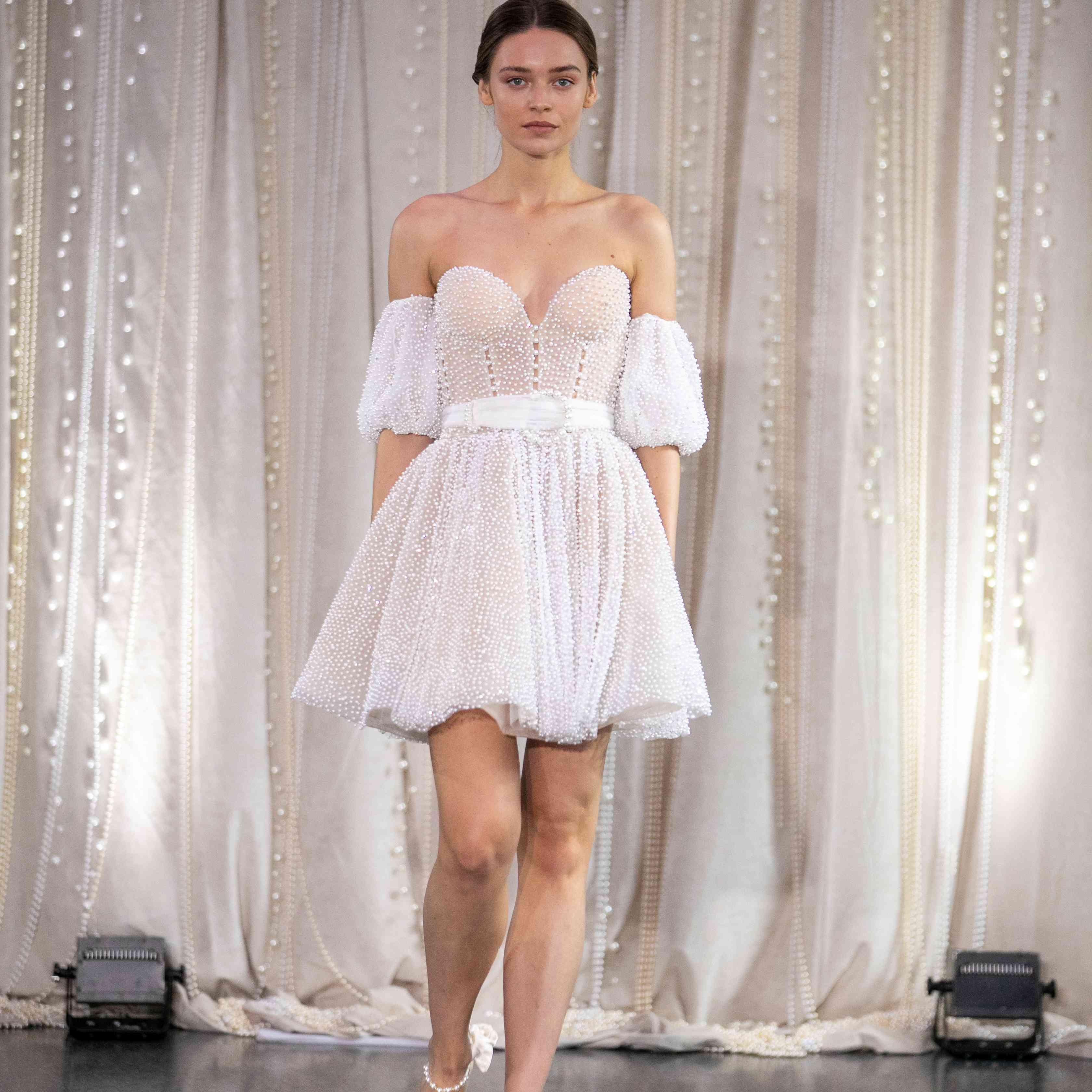 Model in off-the-shoulder mini wedding dress