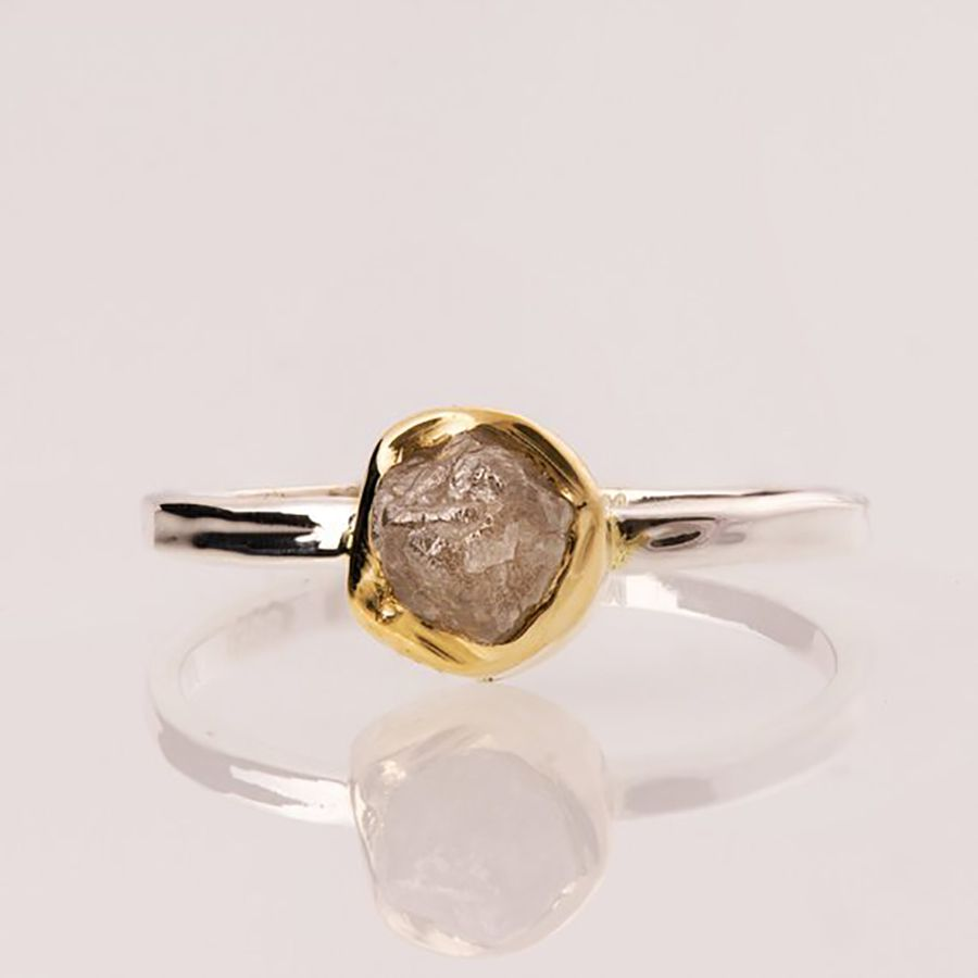 A white gold band with a yellow gold bezel set with a raw diamond