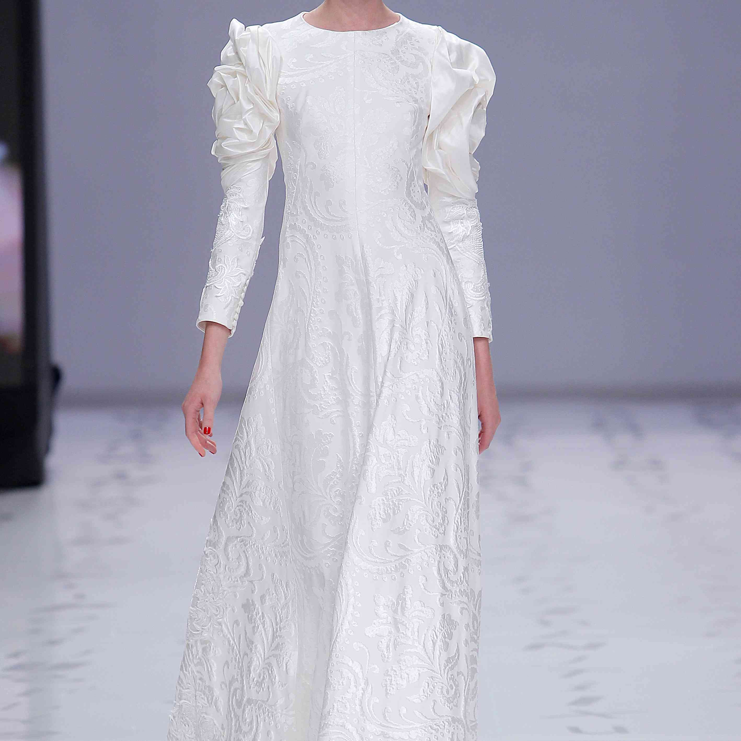 Model in white-on-white damask A-line dress with a round neckline and draped taffeta long sleeves