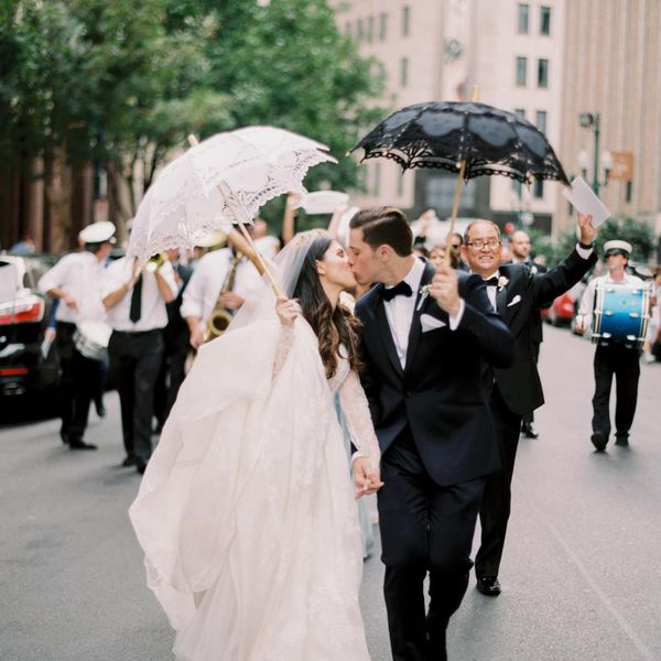 <p>Bride and groom carrying umbrellas</p>