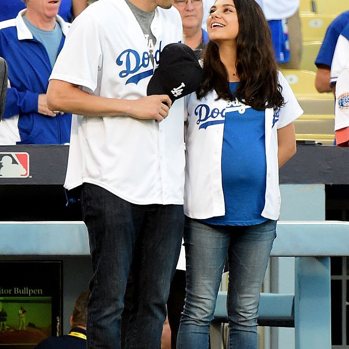 Ashton Kutcher and wife Mila Kunis on the field after they announced the Los Angeles Dodgers starting lineup before game four of the National League Championship Series against the Chicago Cubs at Dodger Stadium on October 19, 2016 in Los Angeles, California.