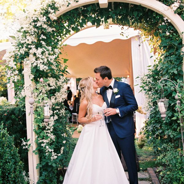 Bride and groom kiss under floral canopy.