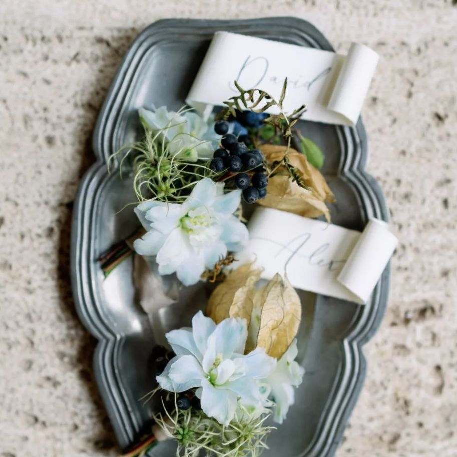 boutonnieres with pale blue oxypetalum and blue berries