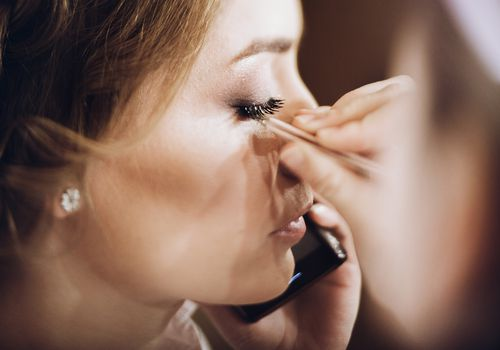 Bride applying false eyelashes with tweezers