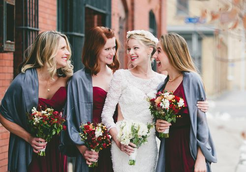 Bride surrounded by bridesmaids in cranberry dresses