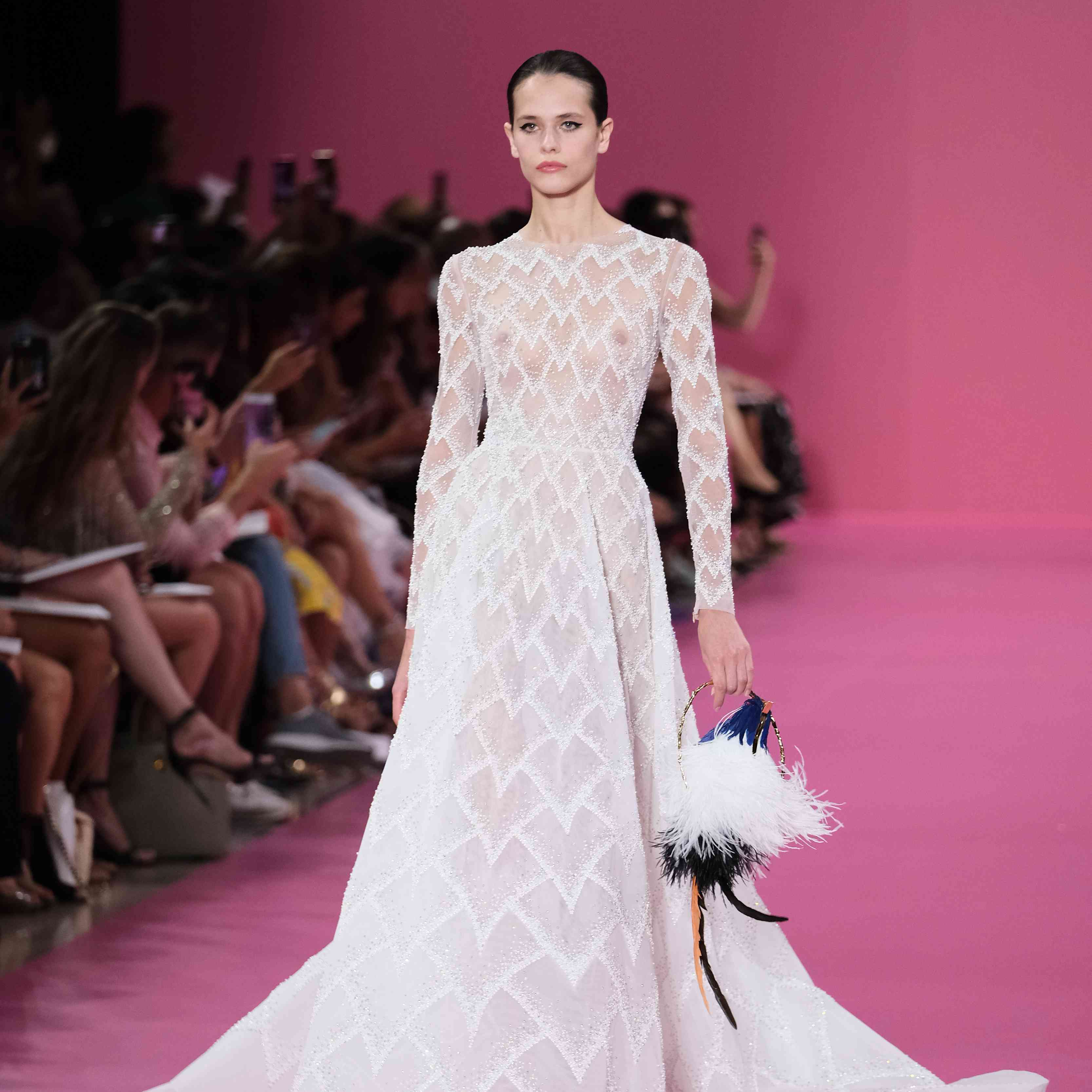 Model in long-sleeved sheer lace white wedding gown