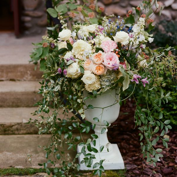 Pot of flowers with roses, greenery, and other summer flowers