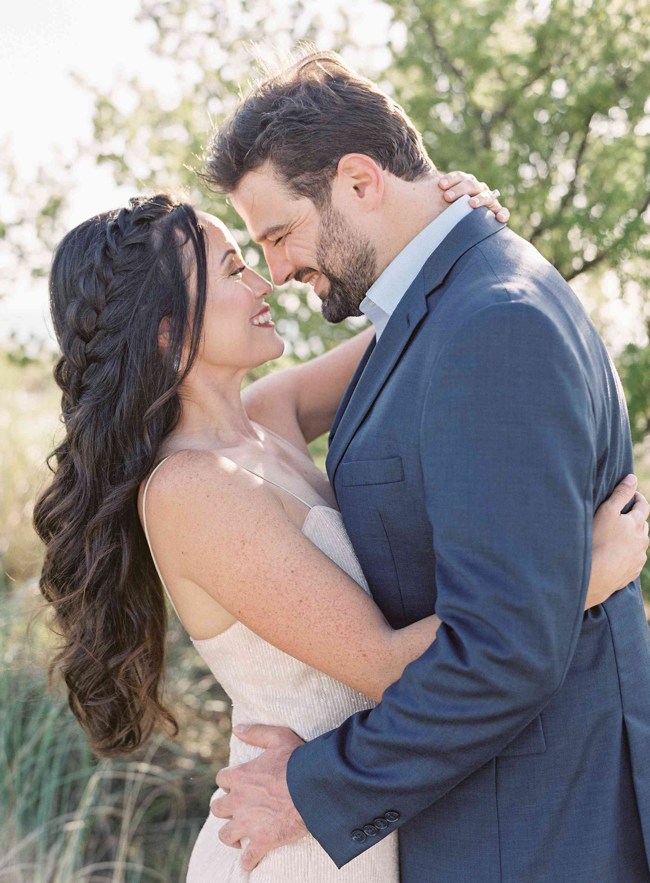 Bride with waterfall braid embracing groom