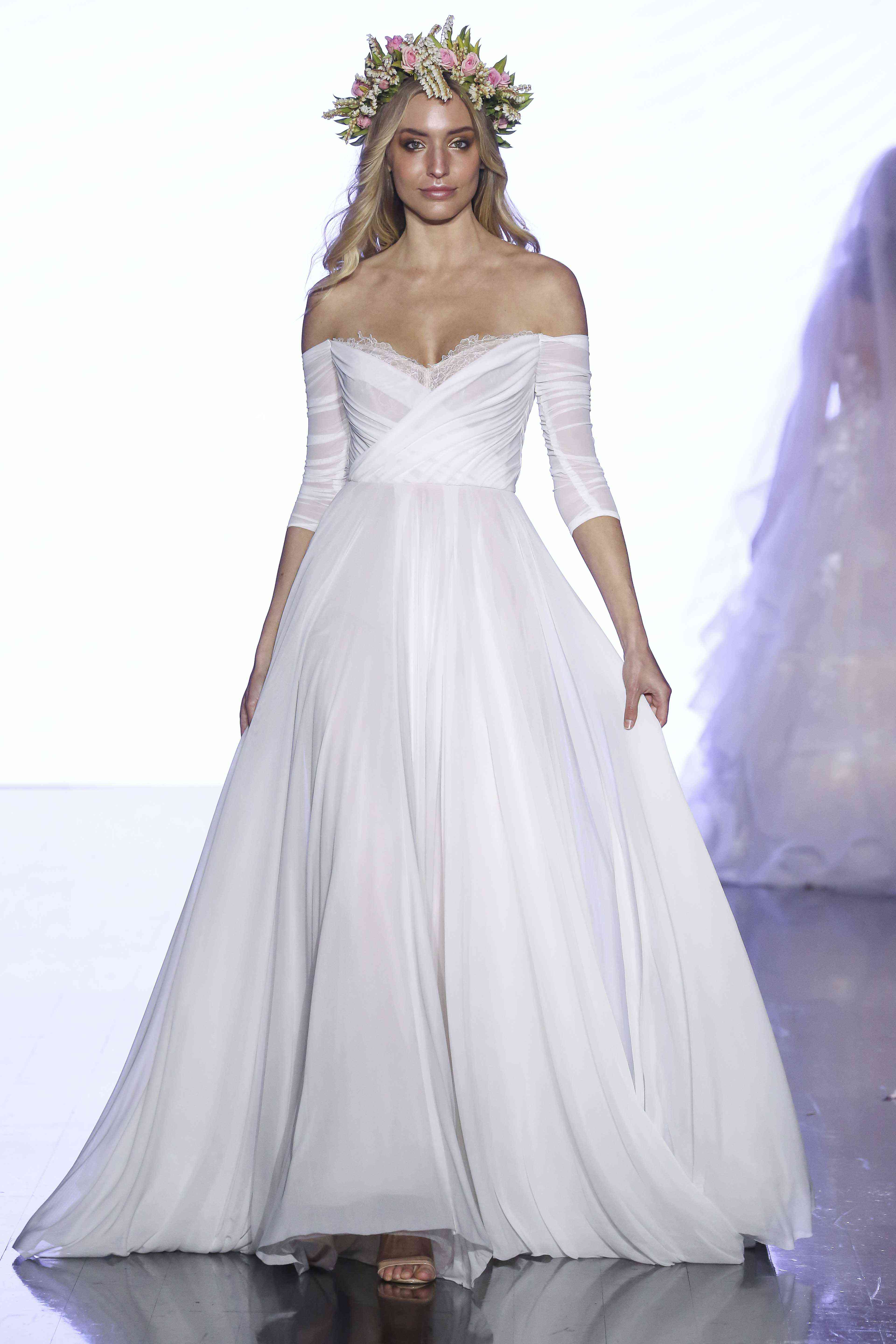 Model in off-the-shoulder three-quarter-sleeve stretch mesh A-line wedding gown with peek-a-boo lace at the bust