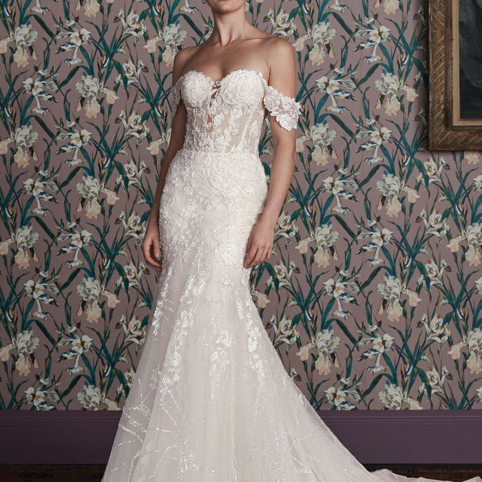 Model in lace mermaid gown with corset bodice and off-the-shoulder sleeves
