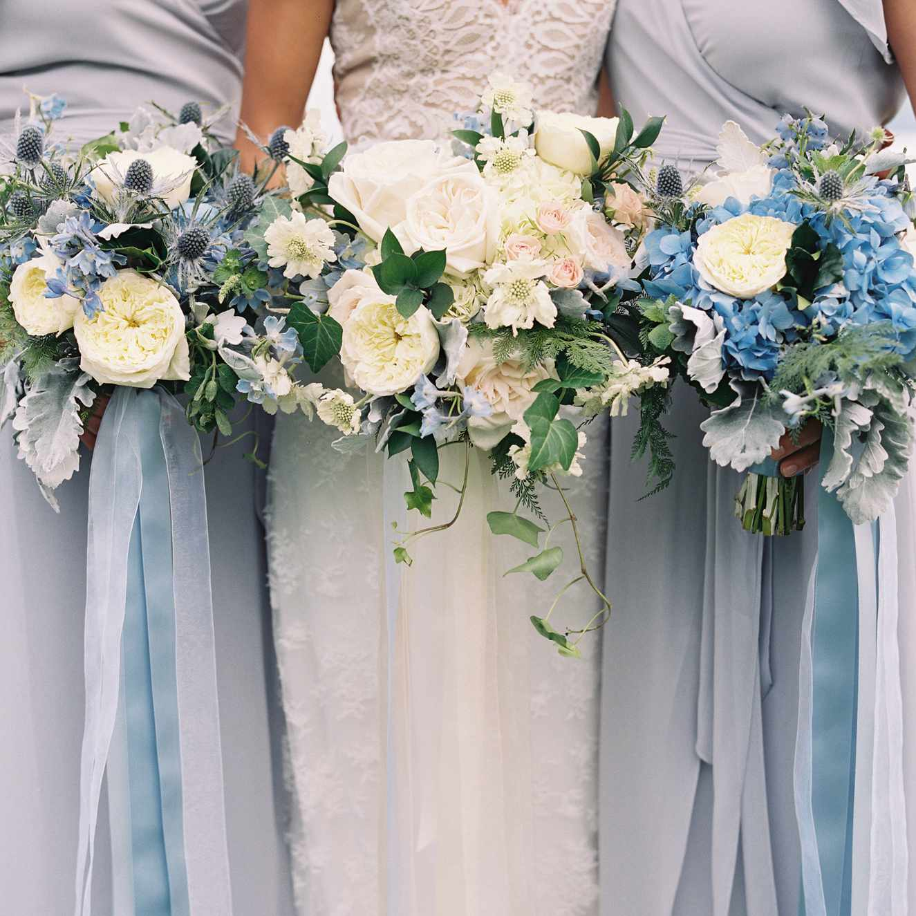 Bride with two bridesmaids holding blue and white bouquets of garden roses, thistle, hydrangea, scabiosa, florabunda roses, dusty miller, ivy, painted fern, delphinium, and flowering mint