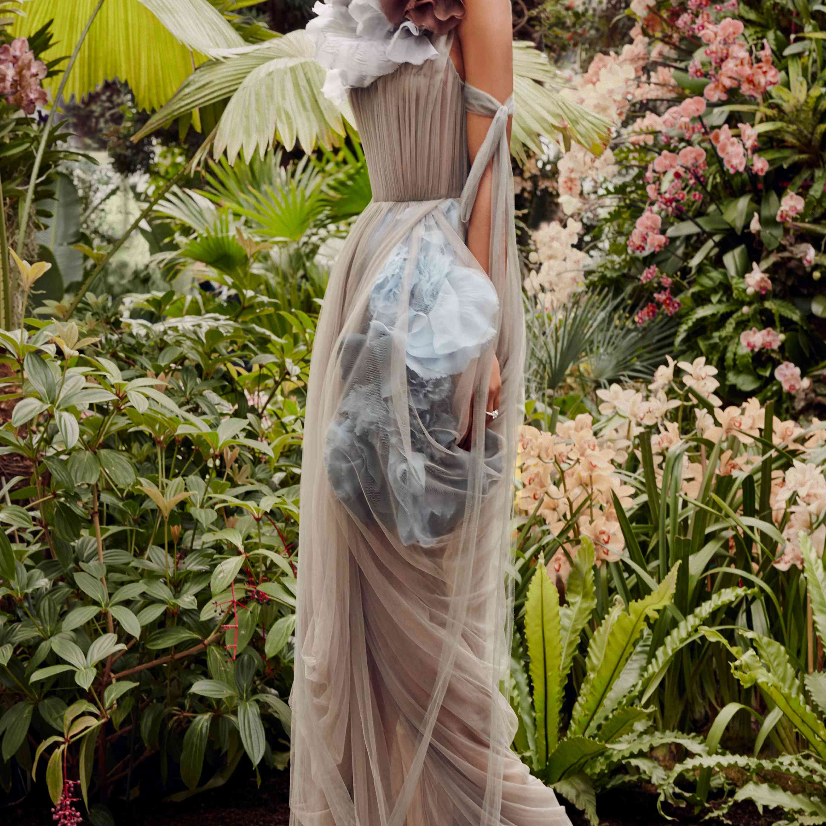Model in a taupe draped tulle gown with blue flowers at the waist and skirt and a white and rust flower at the shoulder