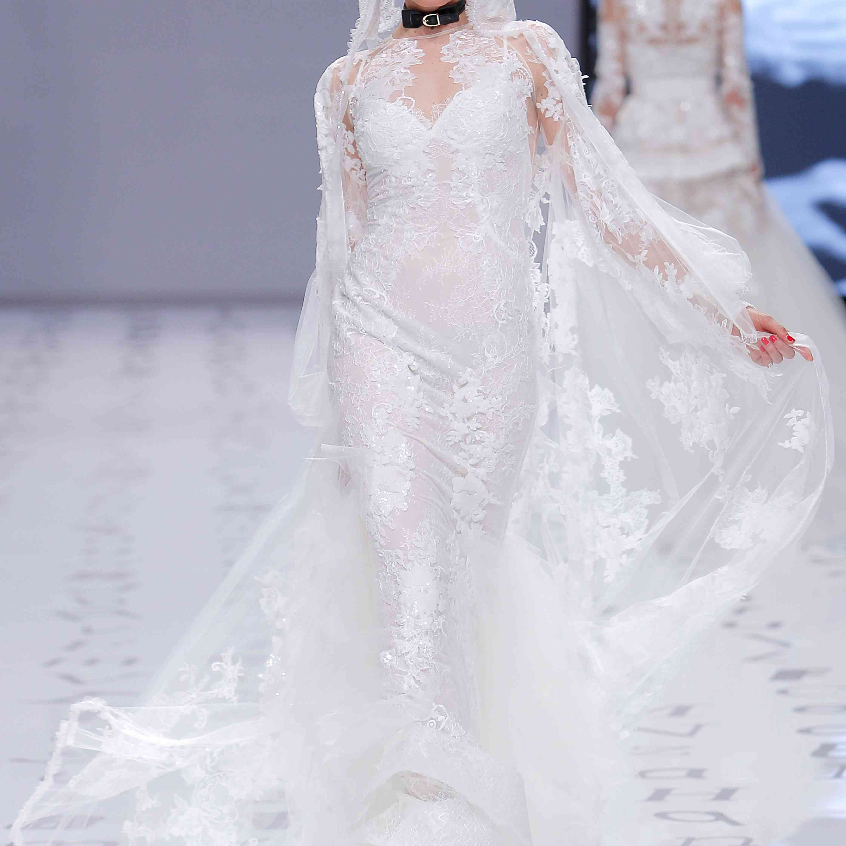 Model in a long-sleeve embroidered lace mermaid dress with an embroidered tulle hooded jacket