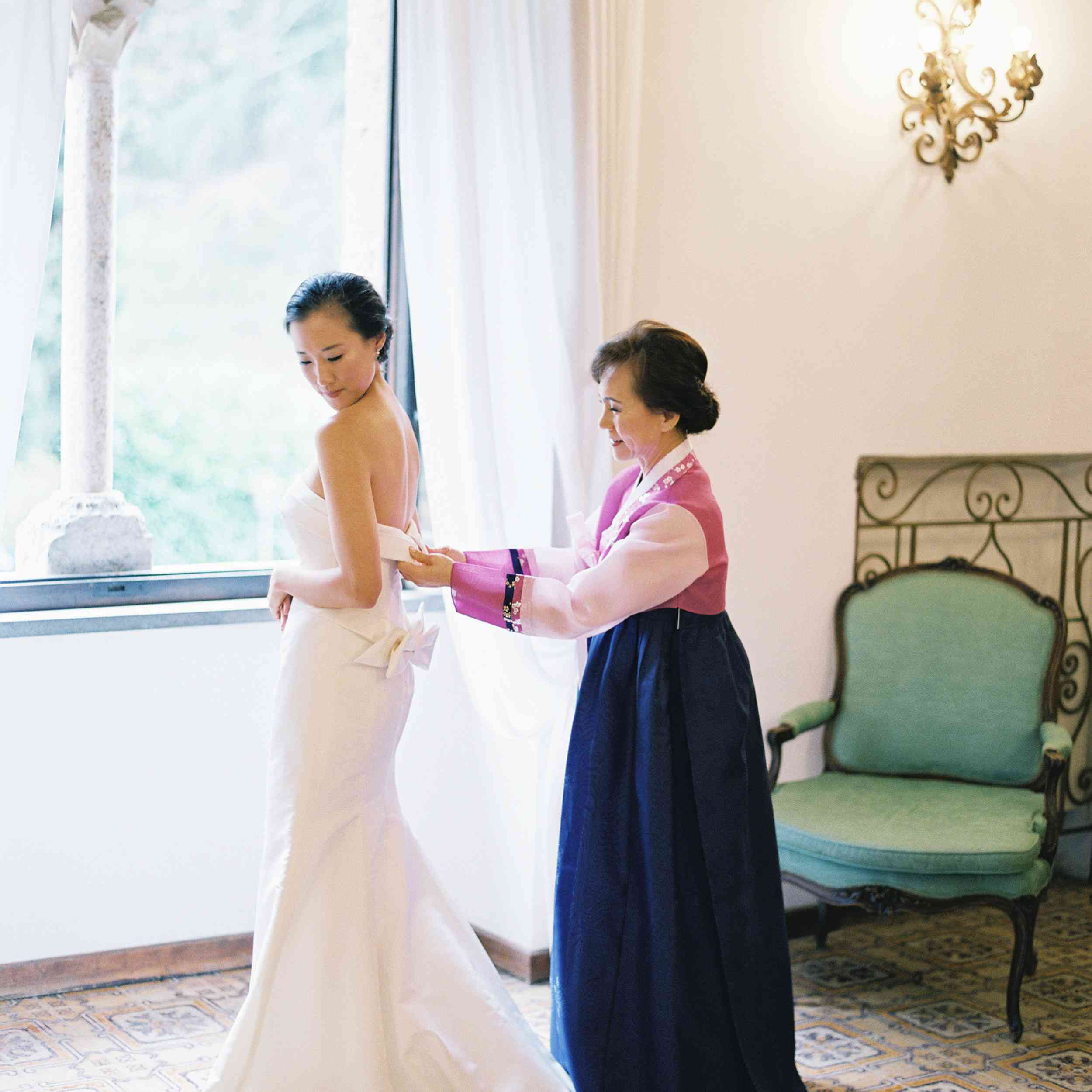 Mom in traditional dress zipping bride into wedding gown