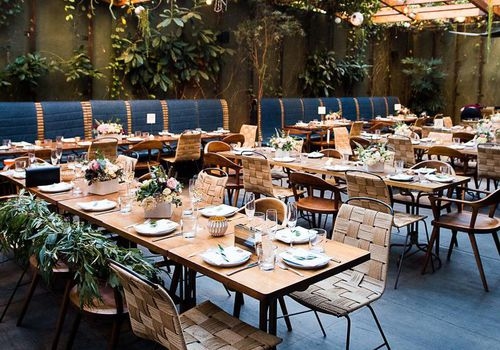 restaurant interior with table settings and greenery