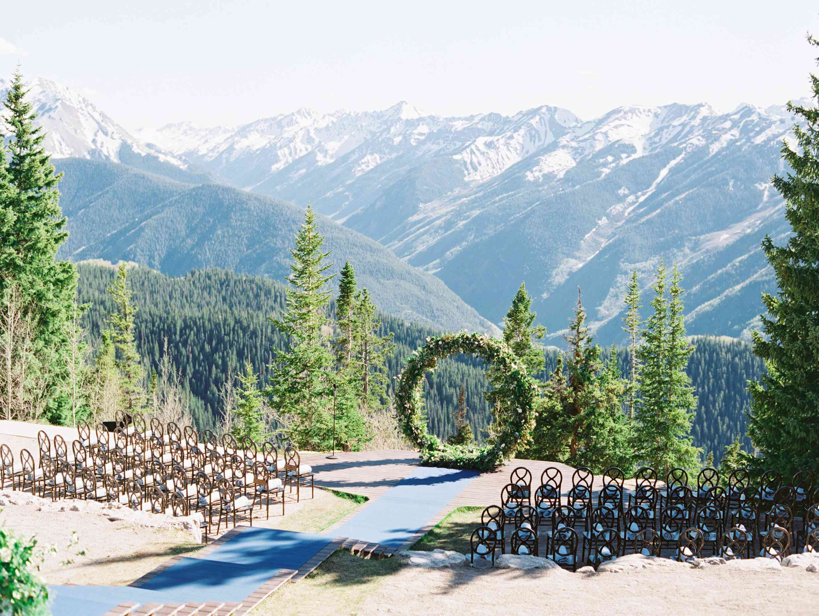 Ceremony in front of mountain view with stairs leading to the circle arch of greenery