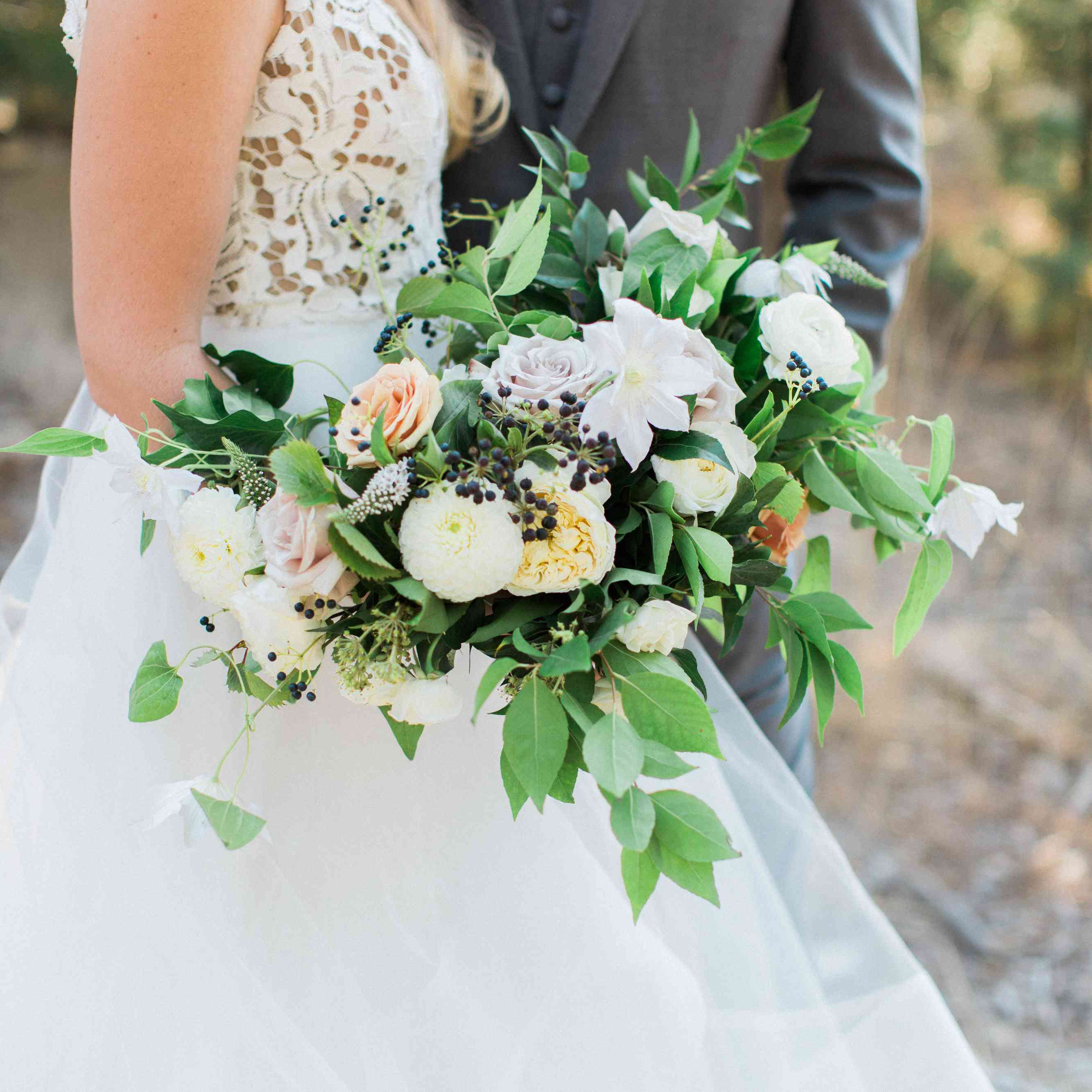 Bride holding bouquet of rose, clematis, dahlia, and veronica with berries