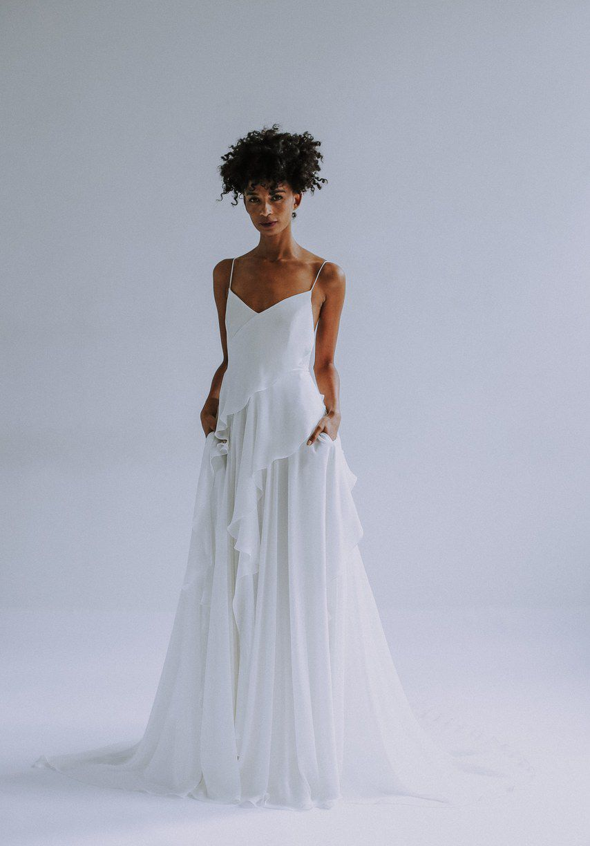 Model in spaghetti strap while wedding gown with layered skirt