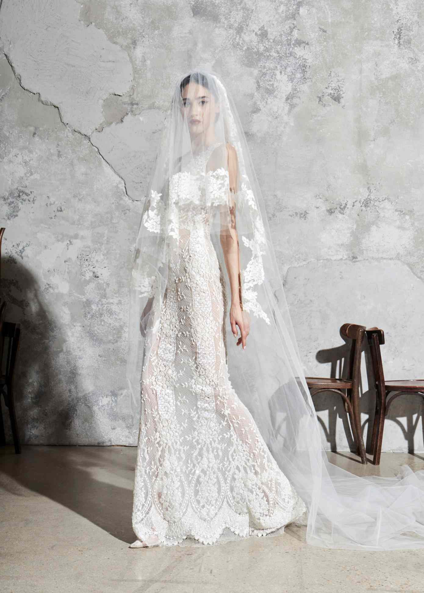 Model in a sleeveless allover lace and tulle sheath dress with a matching veil