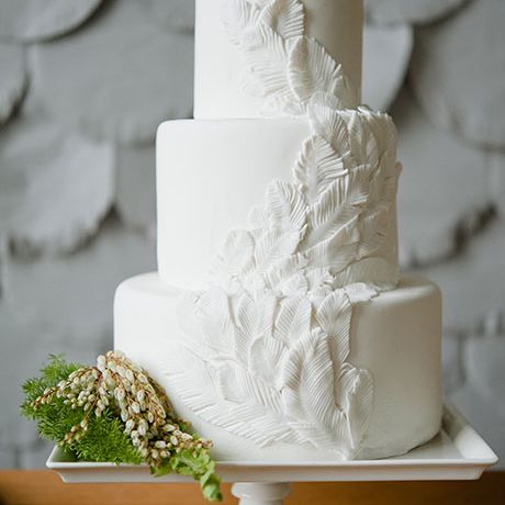 Three-tiered white wedding cake with textured feather detail