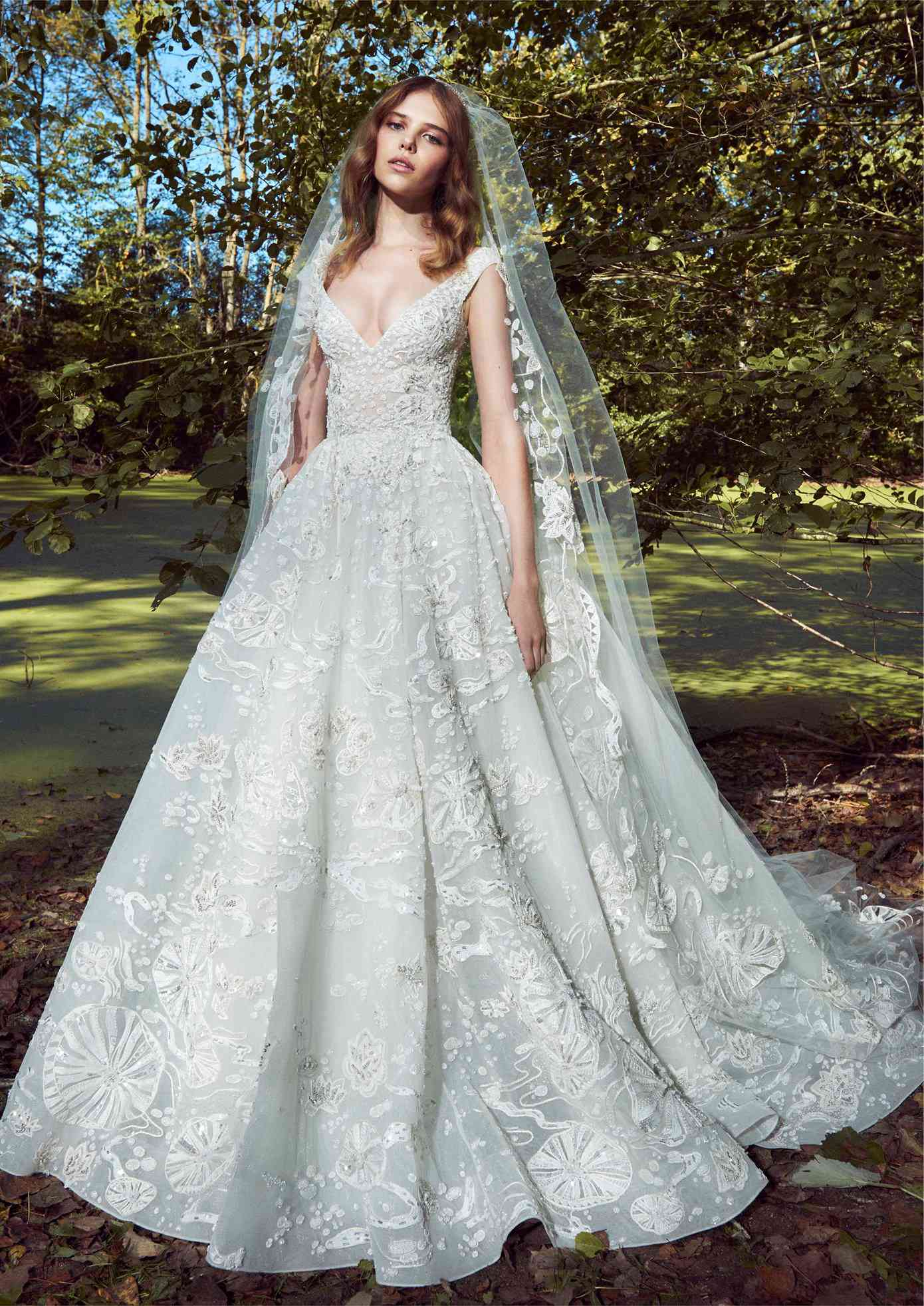 Model in an off-the-shoulder V-neck bateau ballgown with embroidery and beading with a matching veil