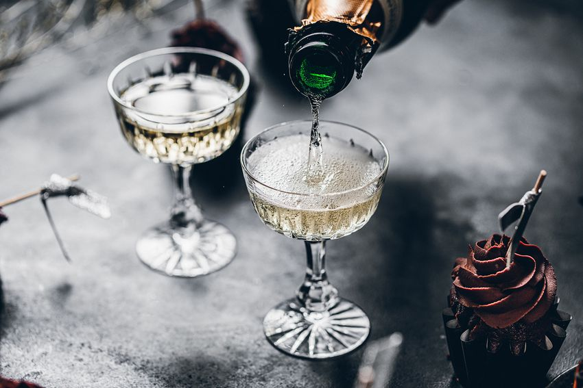 Close-up of pouring champagne in a glasses over black table with cup cake