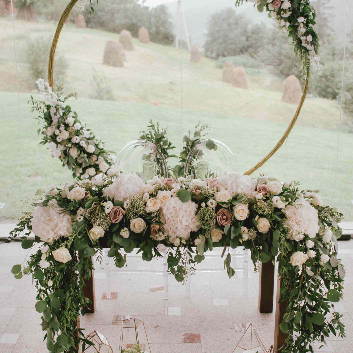 Sweetheart table with lush floral accents and circular installation