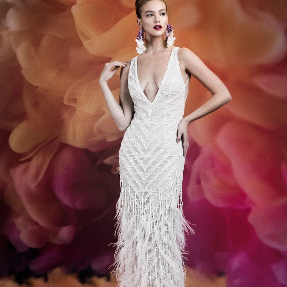 Model in beaded wedding gown with plunging neckline and feathered skirt