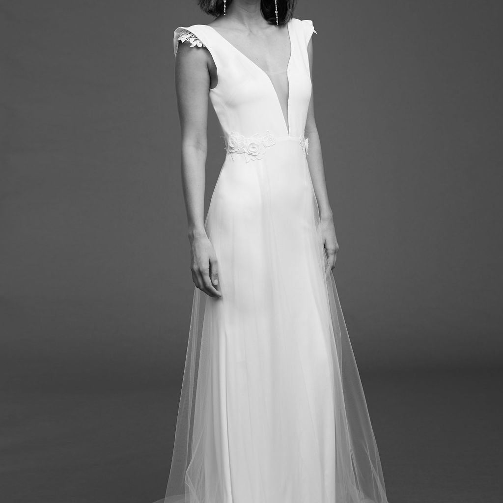 Model in crepe dress with plunging illusion neckline, cap sleeves, floral appliques and tulle overskirt