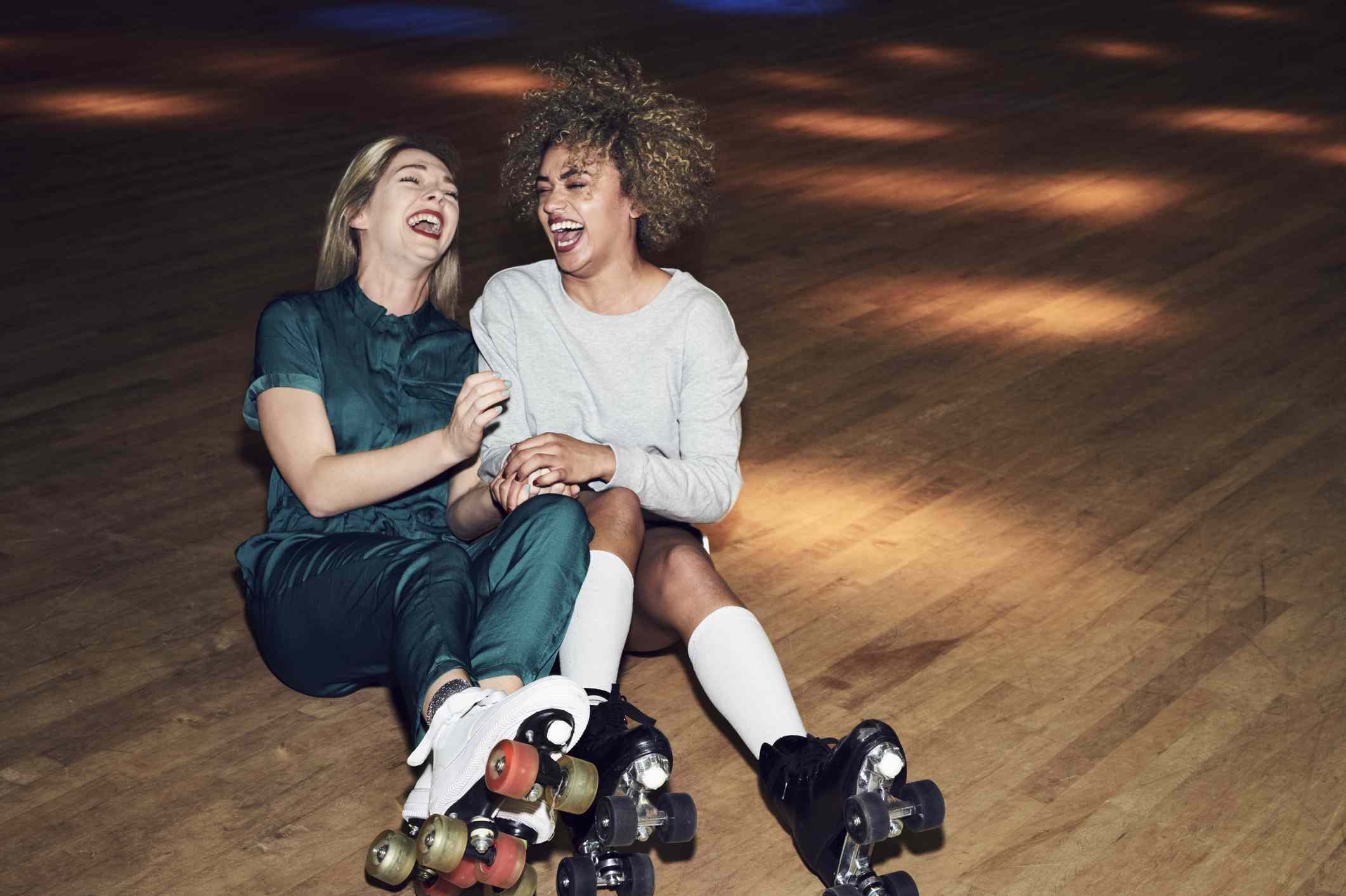 Two girls sitting on the floor of a roller skating rink laughing