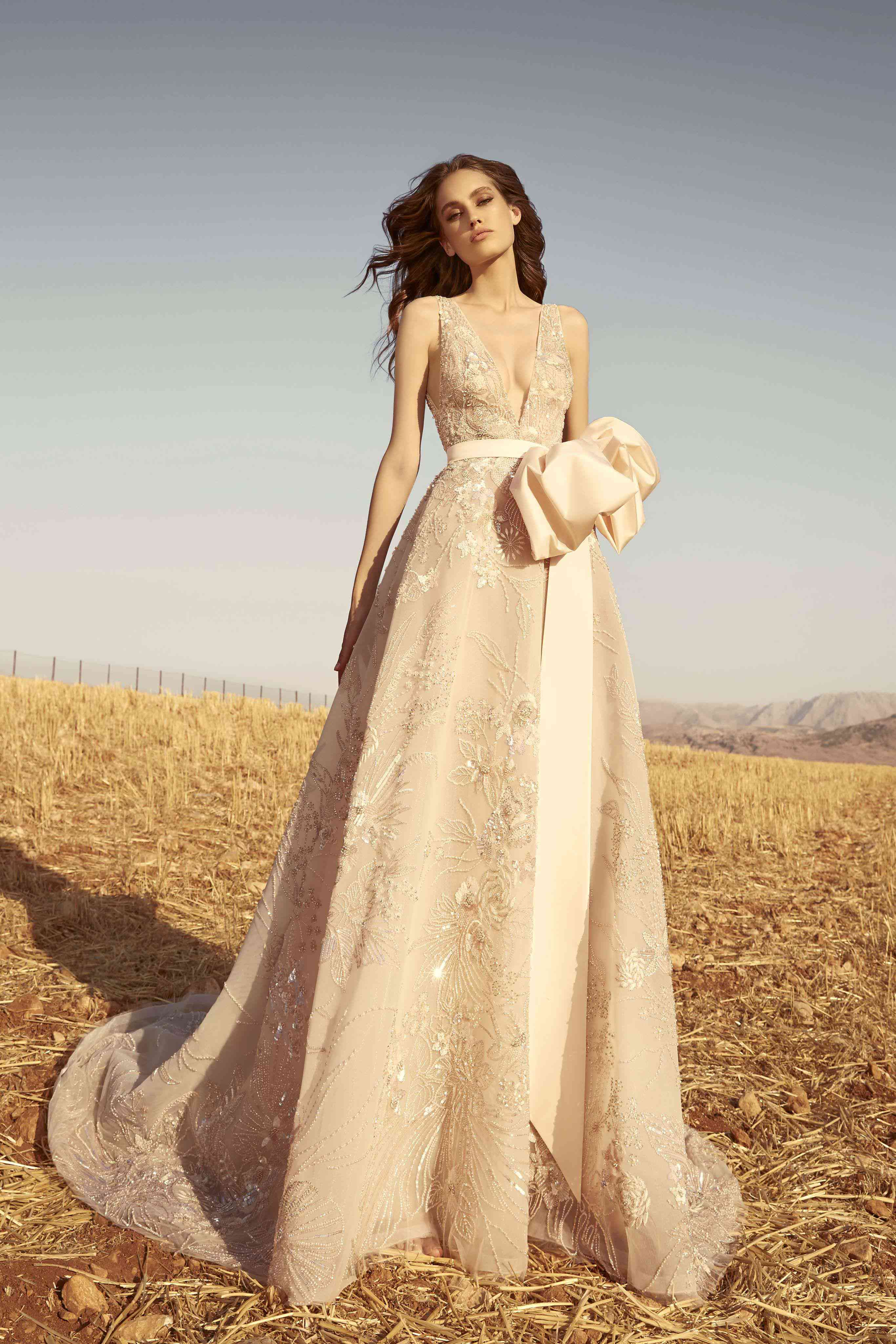 Model in a fully embroidered shell tulle dress with taffeta belt bow and plunging neckline