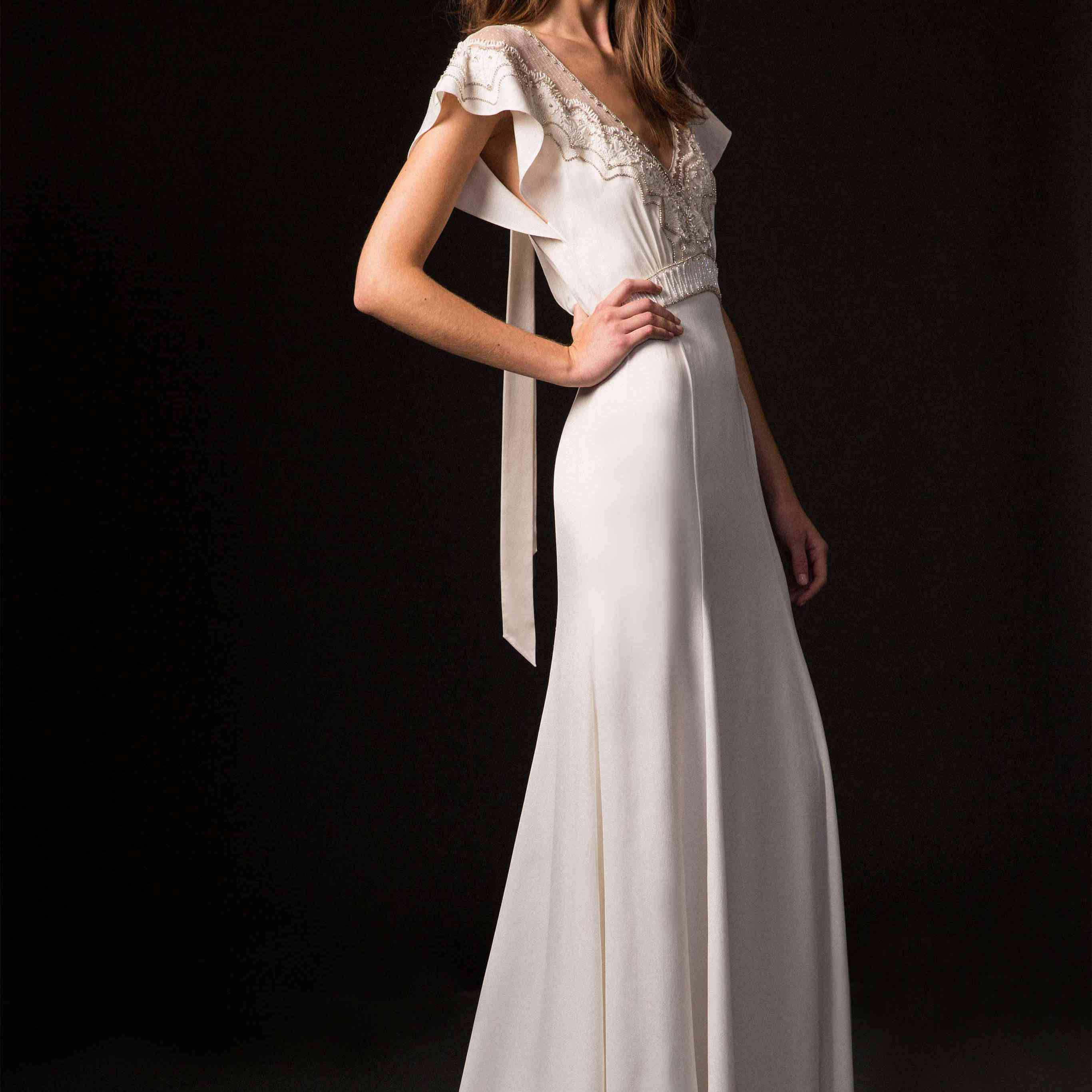 Model in satin sheath dress with beaded detail on the bodice and flutter sleeves