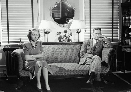 Man and woman on opposite sides of a couch, black and white