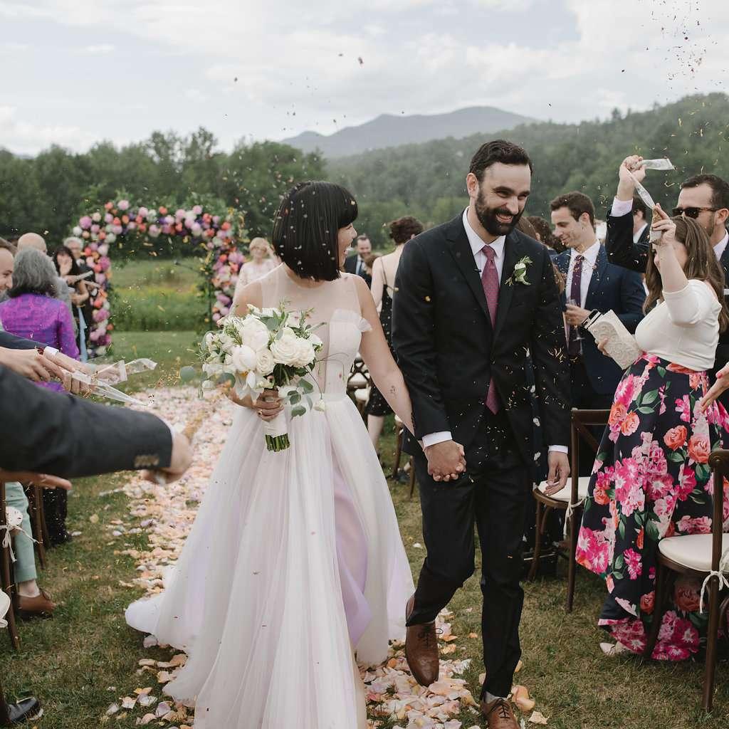 Bride and groom walking up the flower petal aisle
