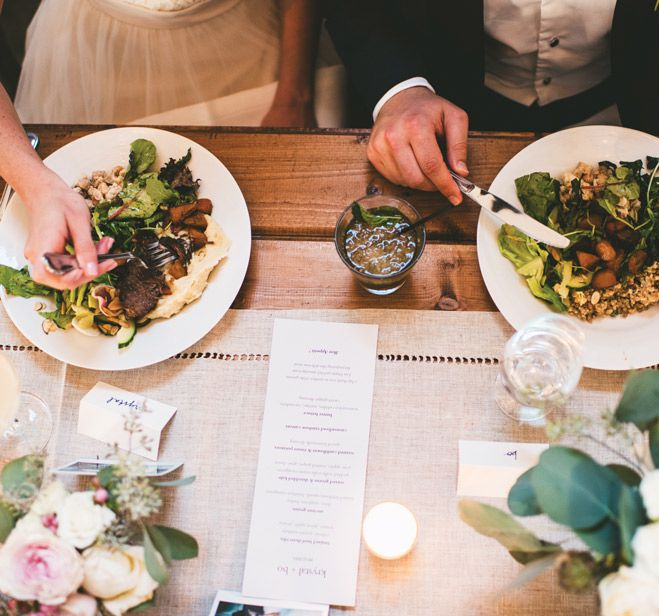 <p>A couple eating entrees with a dinner menu.</p>