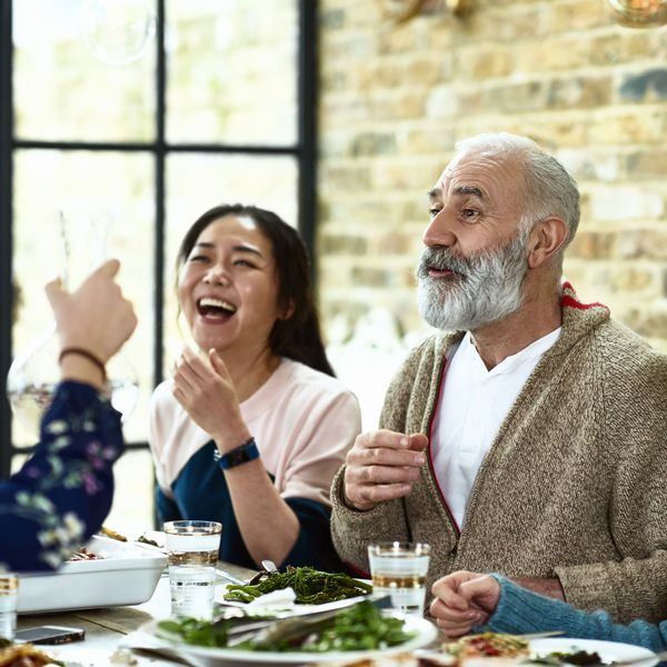 Cheerful mature man telling story over dinner with family laughing