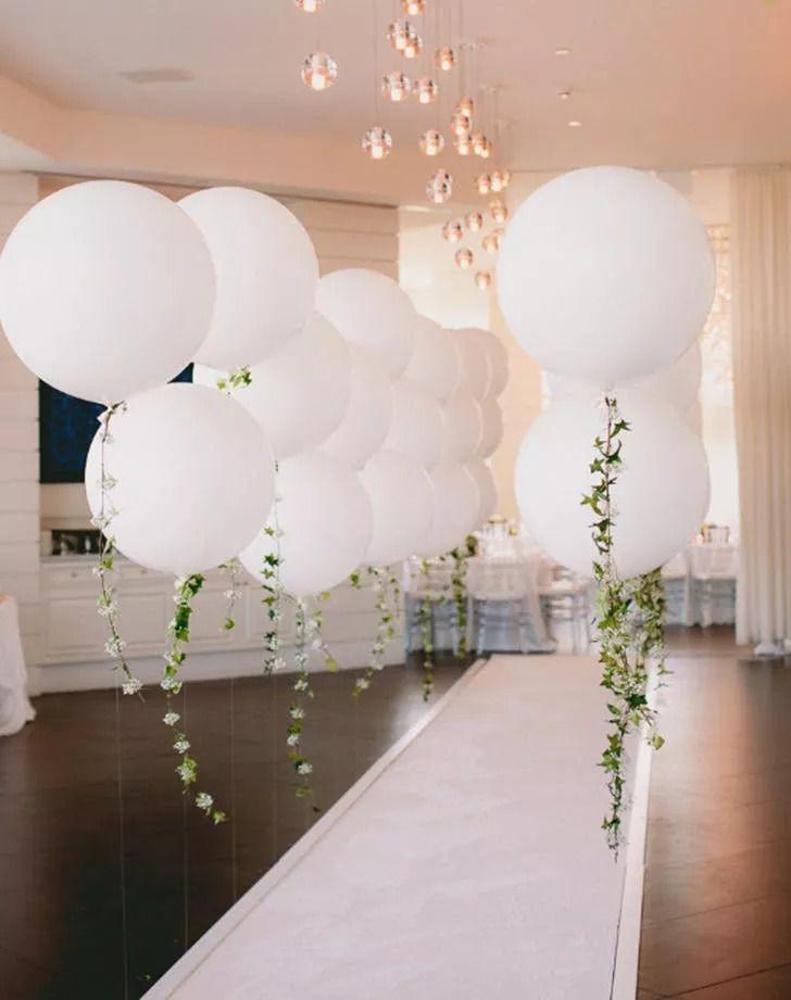 Hanging white balloons with fresh greenery