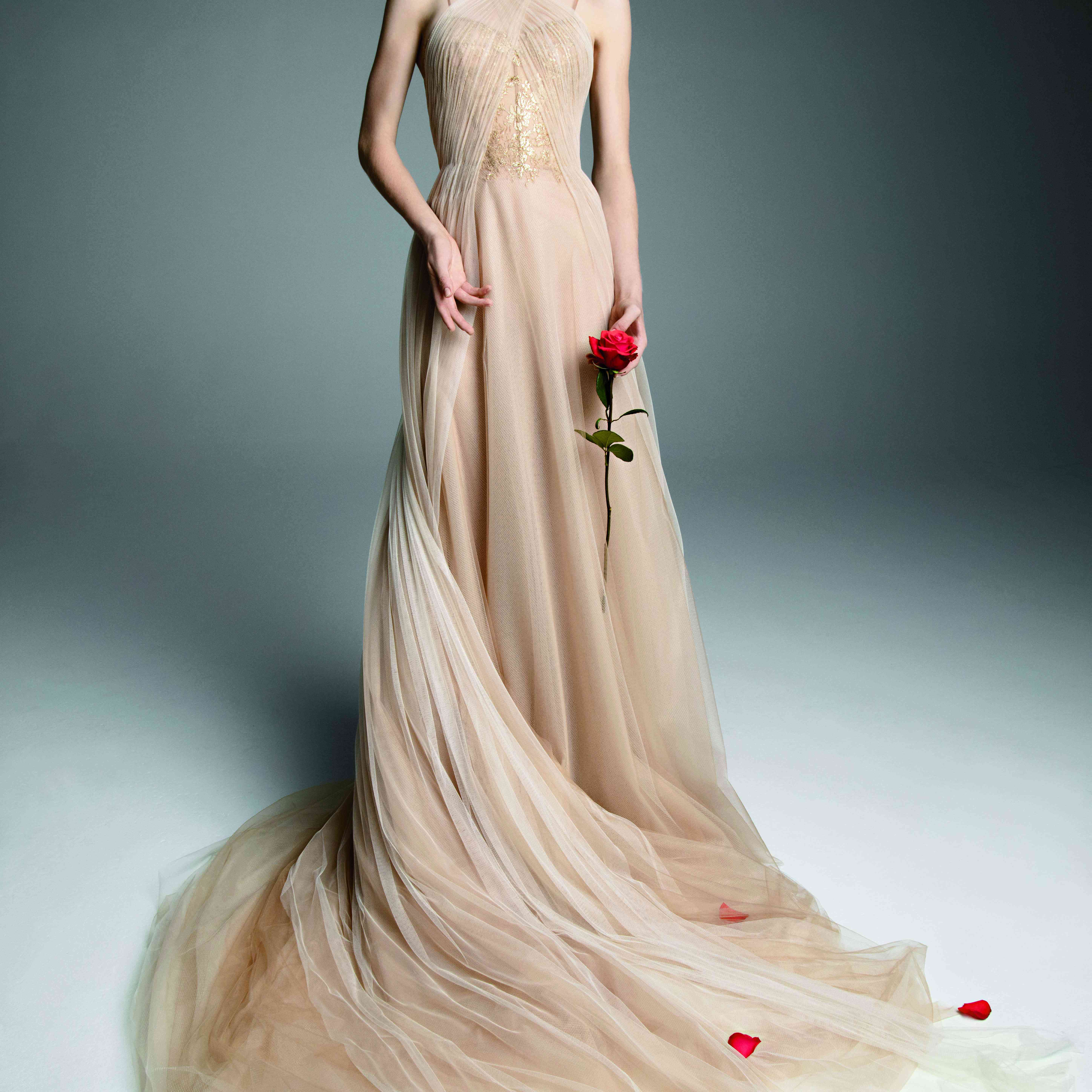 Model in a nude tulle A-line gown with a halter neckline