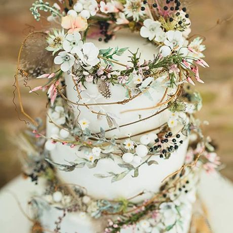 A three-tiered wedding cake crawling with woodland vines and flowers by Amy Swann Cakes