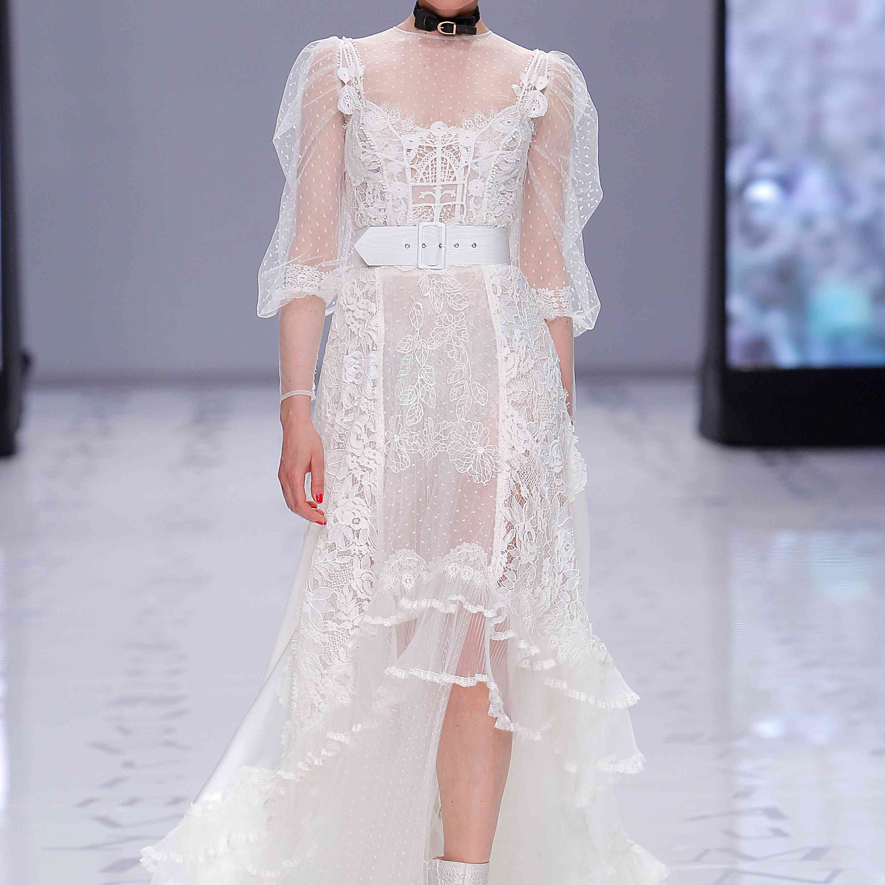 Model in lace and dotted tulle high-low wedding dress with a high neckline, three quarter sleeves, and a ruffled skirt hem