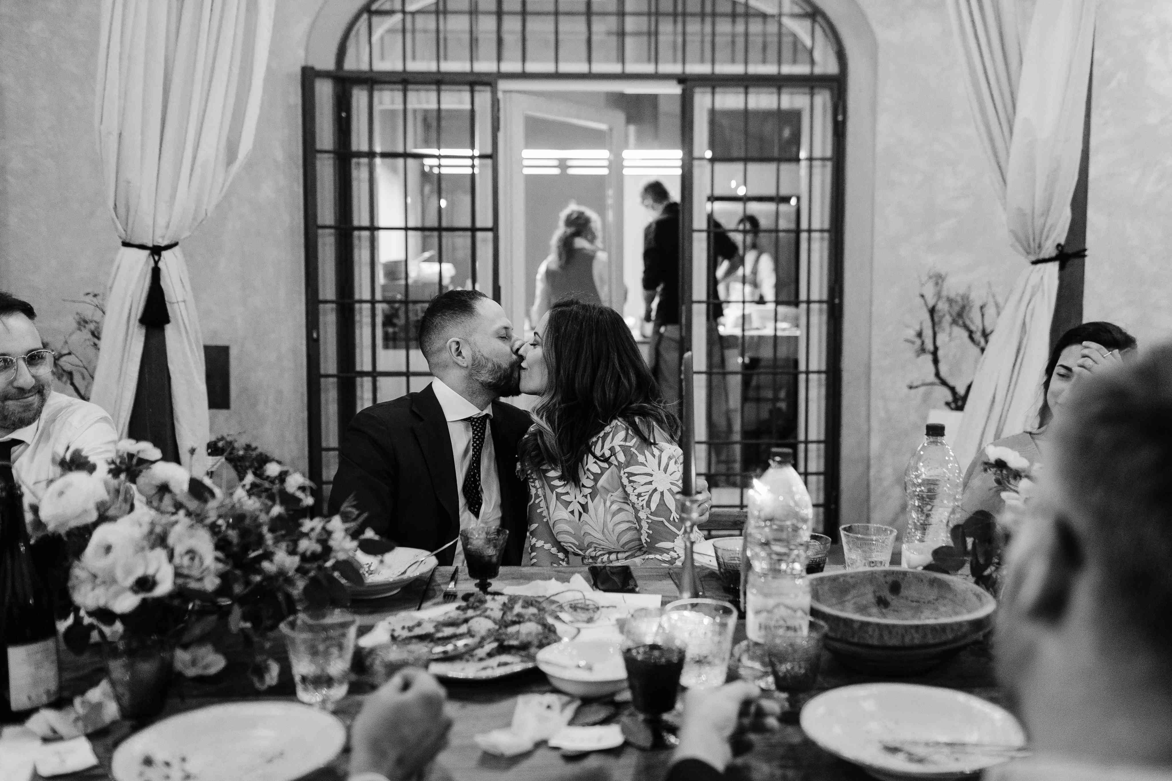 <p>bride and groom kissing at dinner</p><br><br>