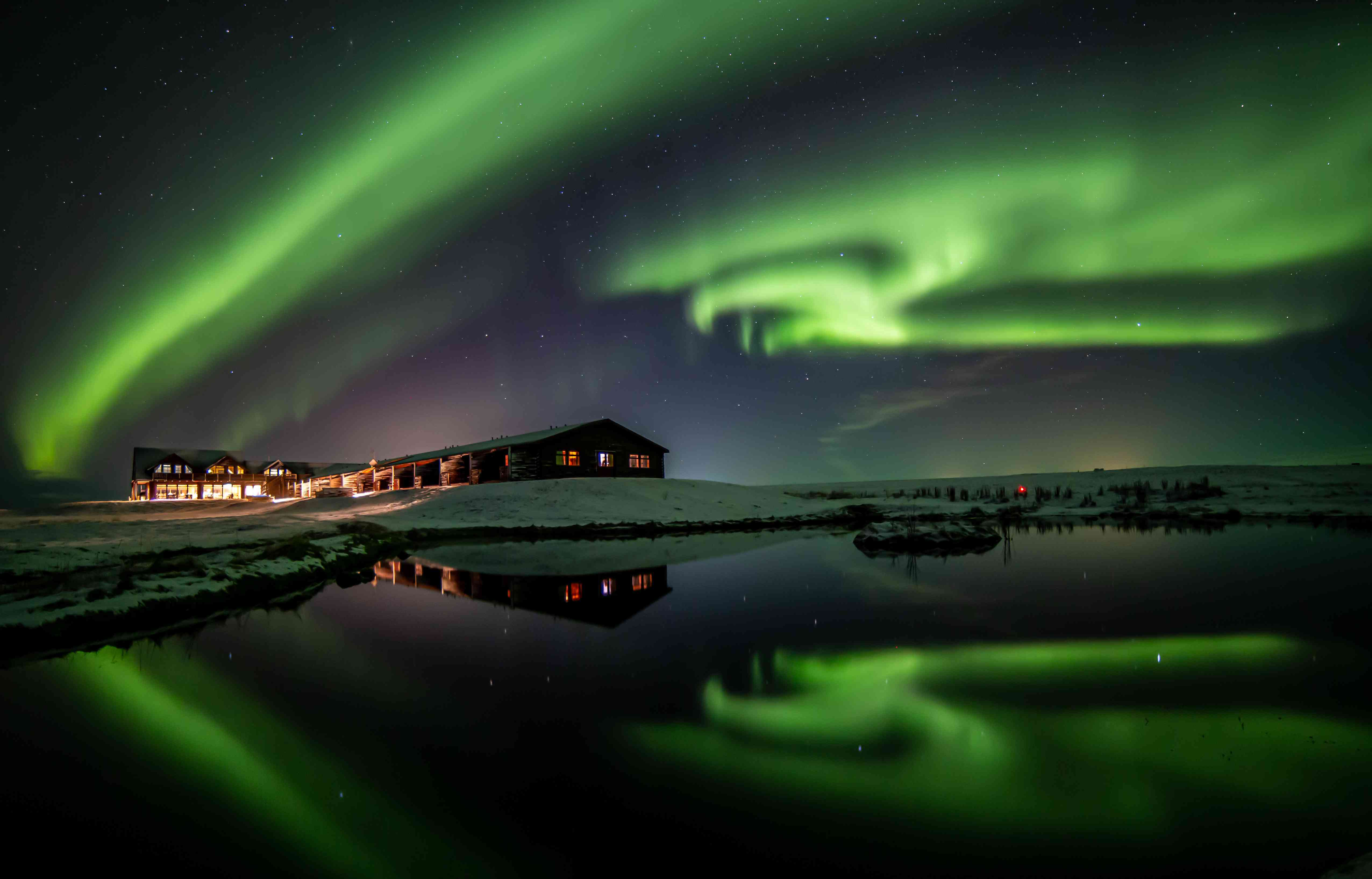Views of the Northern Lights over the water at Hotel Range in Hella, Iceland