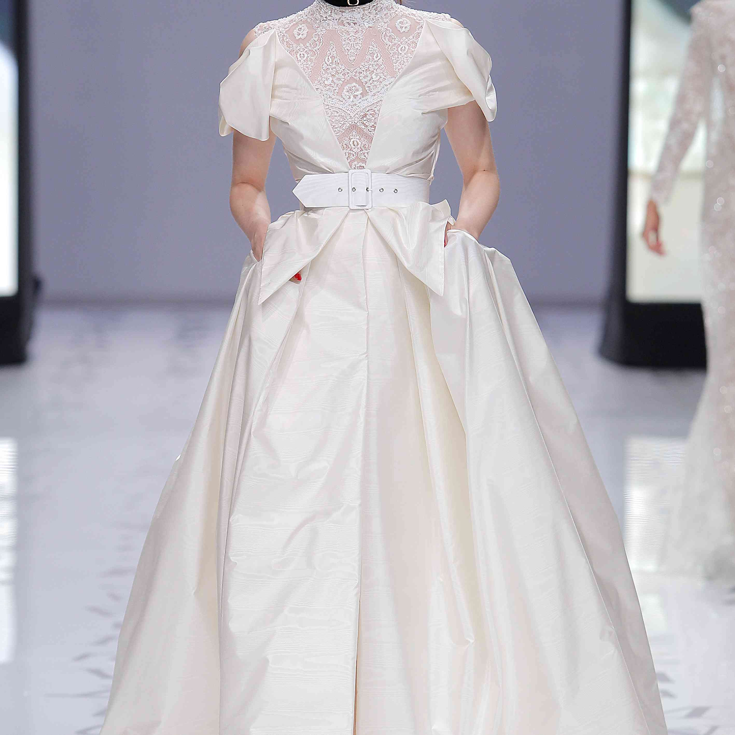 Model in a multi-piece satin ballgown with a rhinestoned lace bodice and a thick white belt at the waist