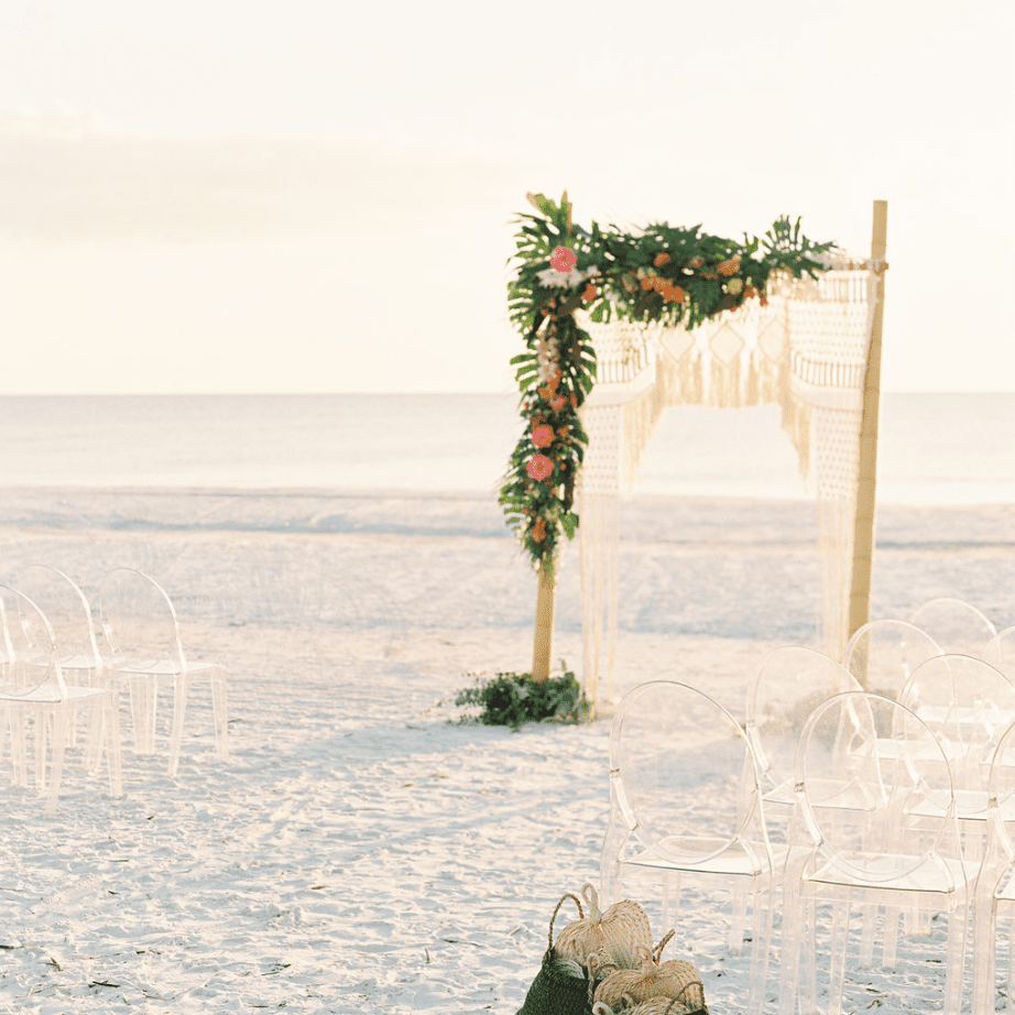 Beach wedding with clear chairs
