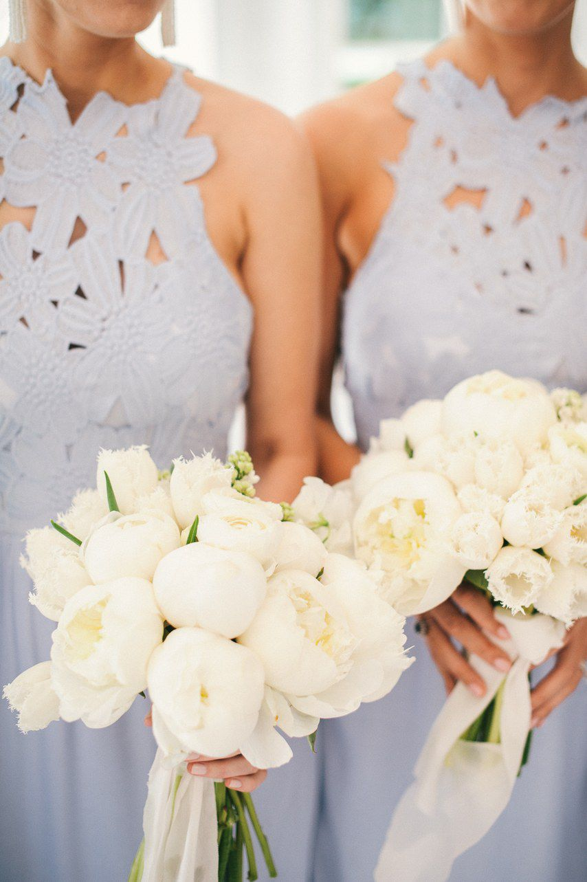 Two bridesmaids in floral cutout bridesmaid gowns holding white rose bouquets