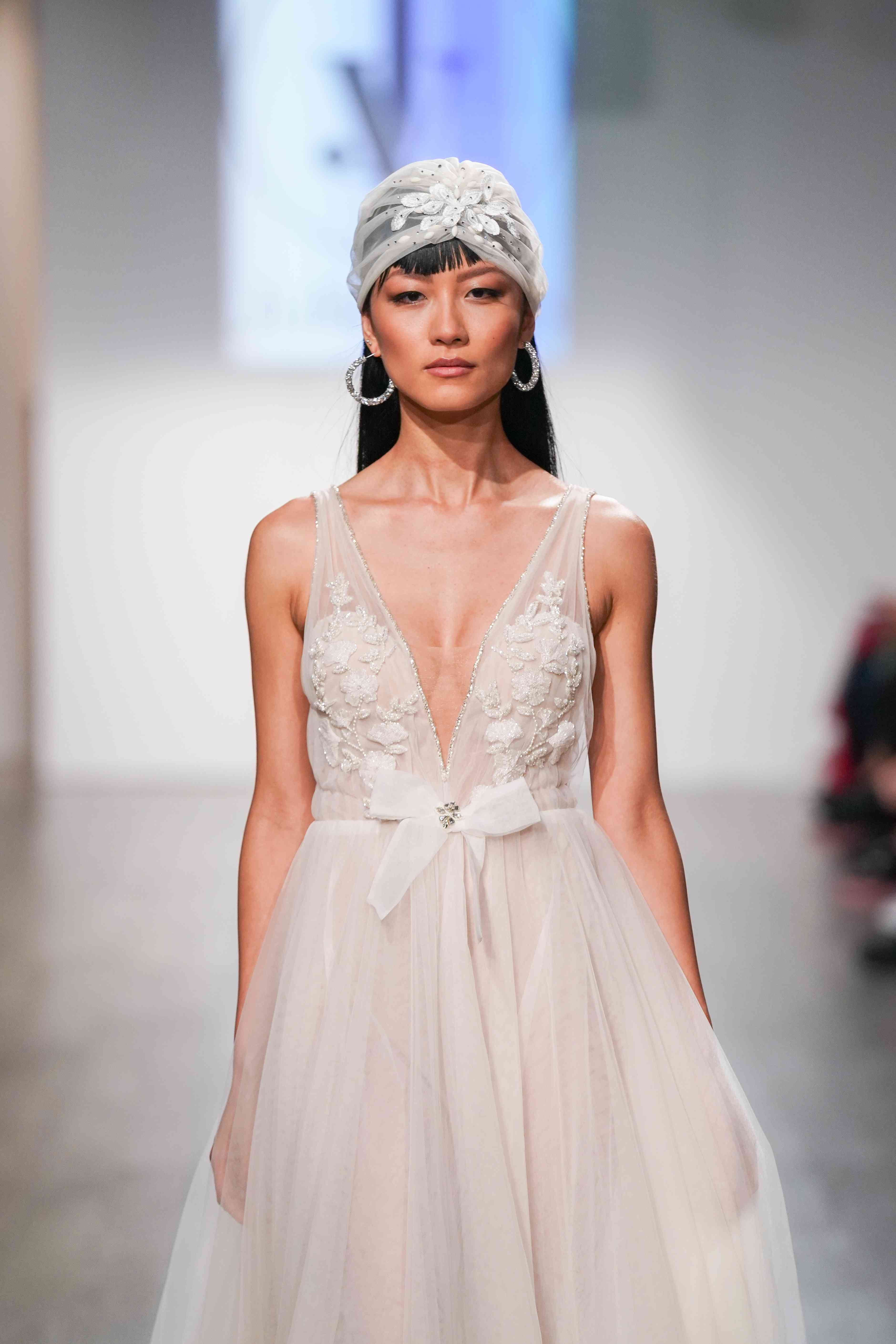 Model in sleeveless wedding dress with bow