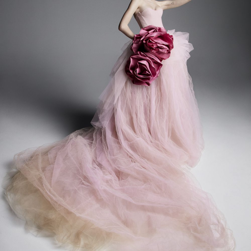 Model in strapless pink tulle ballgown with a nude tulle underskirt and two dark pink floral accents at the waist